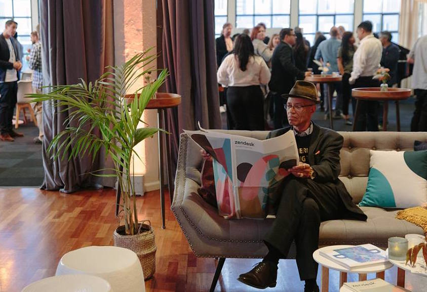 A guest reads the Zendesk newspaper at their rebrand launch event