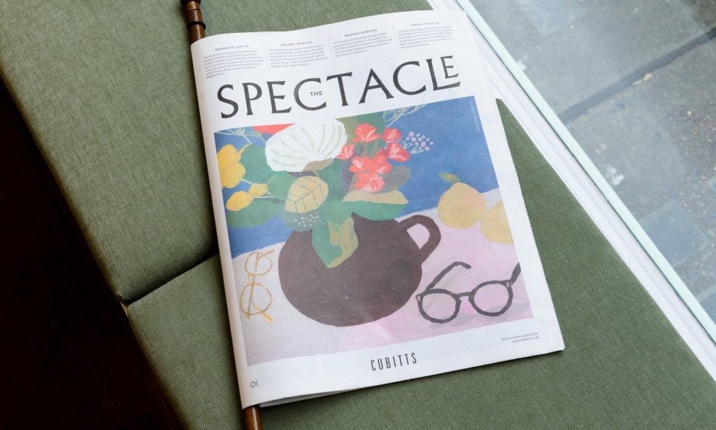 Issue 1 of the The Spectacle newspaper from Cubbits. Cover shows an illustration of glasses next to a vase of flowers.